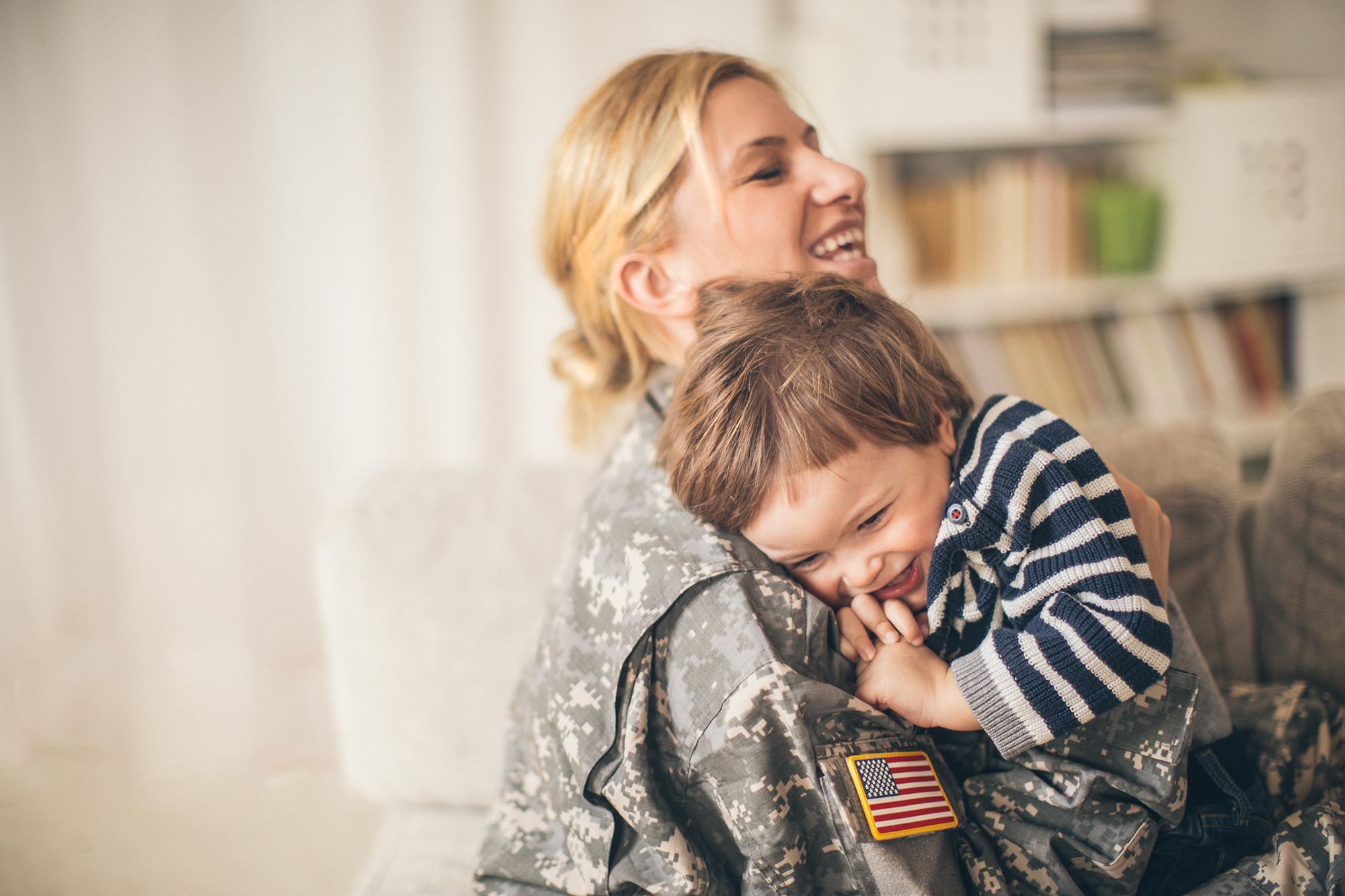 Photo of smiling young woman soldier and her son seeing after a long time and enjoying in their living room. Woman is sitting on the sofa and hugging him