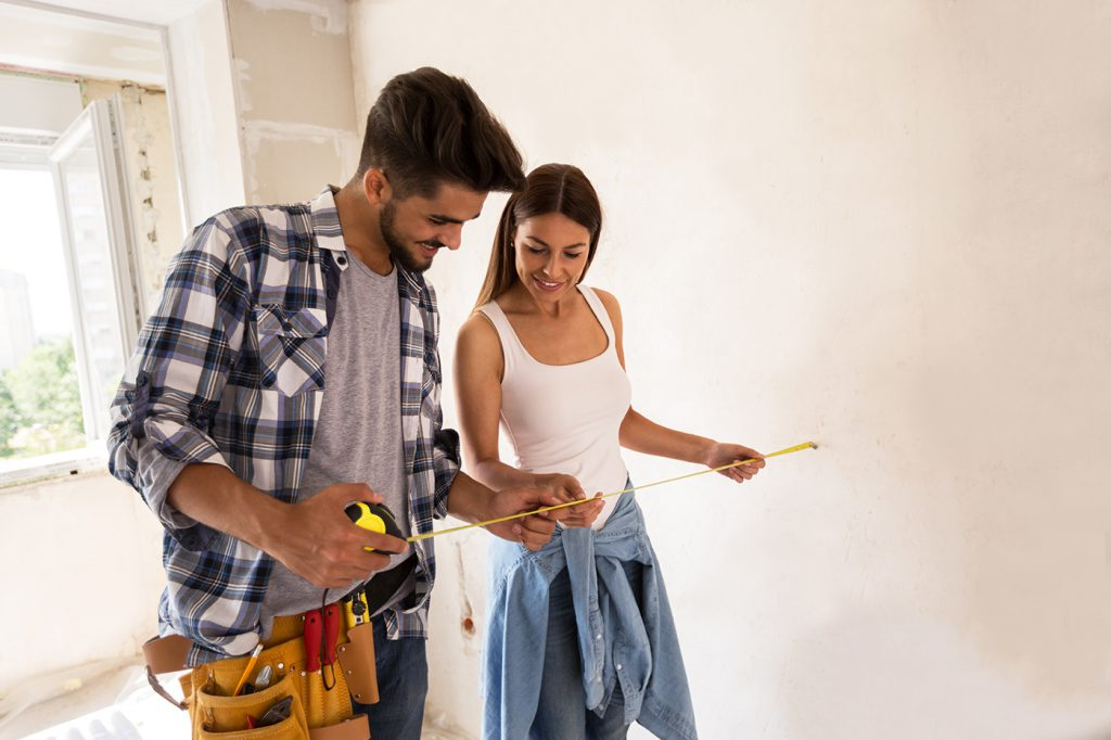 Lovely young couple with tape measure, renovation concept
